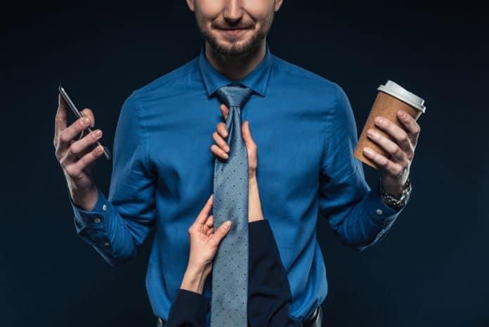 Mand med mobil, slips og kaffe klar til arbejde